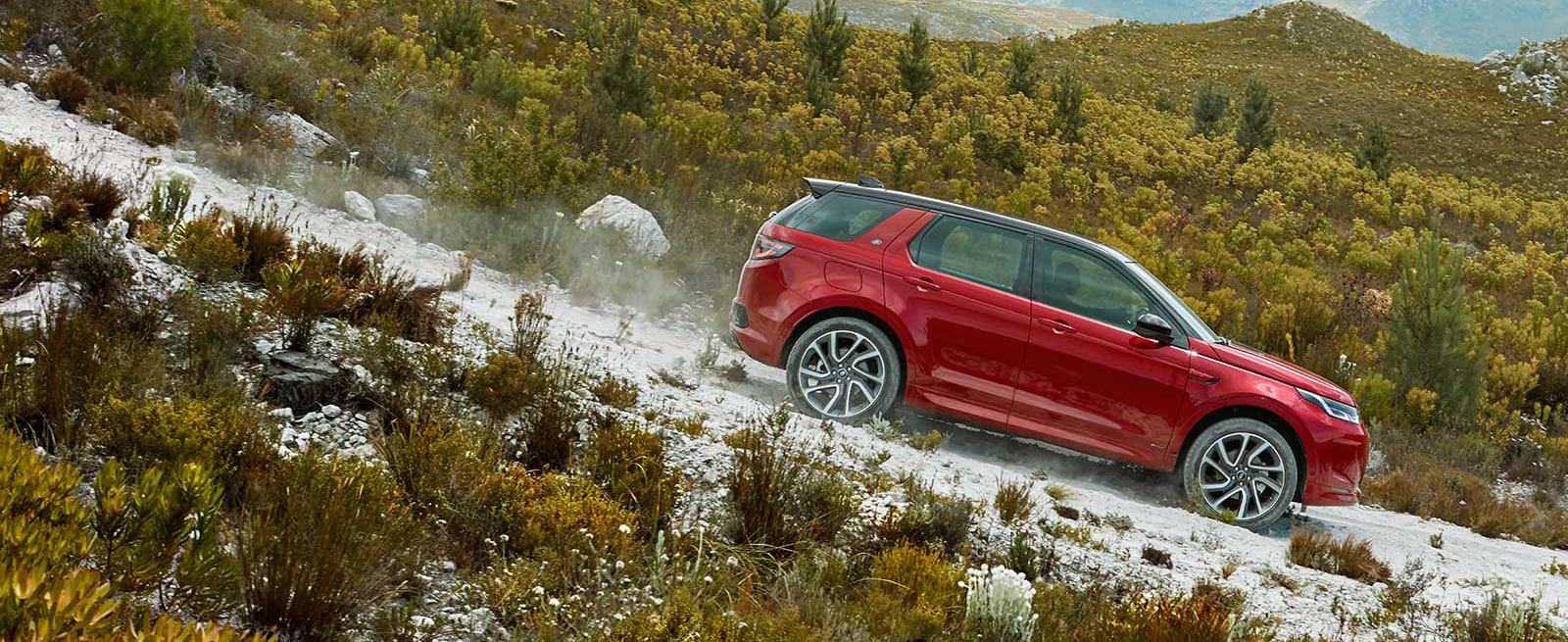 Red Discovery Sport Driving Off-road Down A Hill