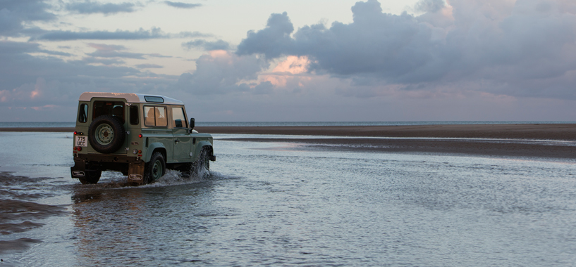 Classic Green Defender 90 driving along the seafront