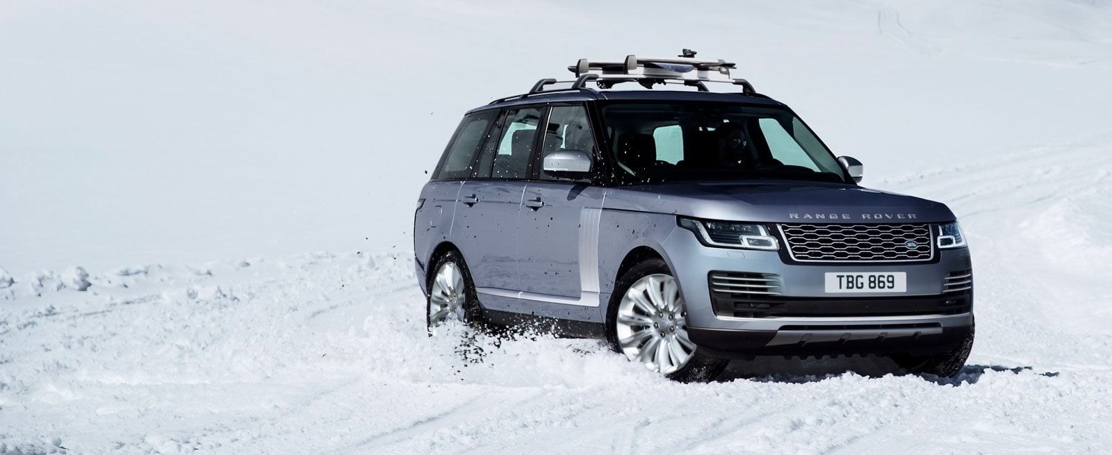 Blue Range Rover with Roof Rack Driving Through Snowy Terrain