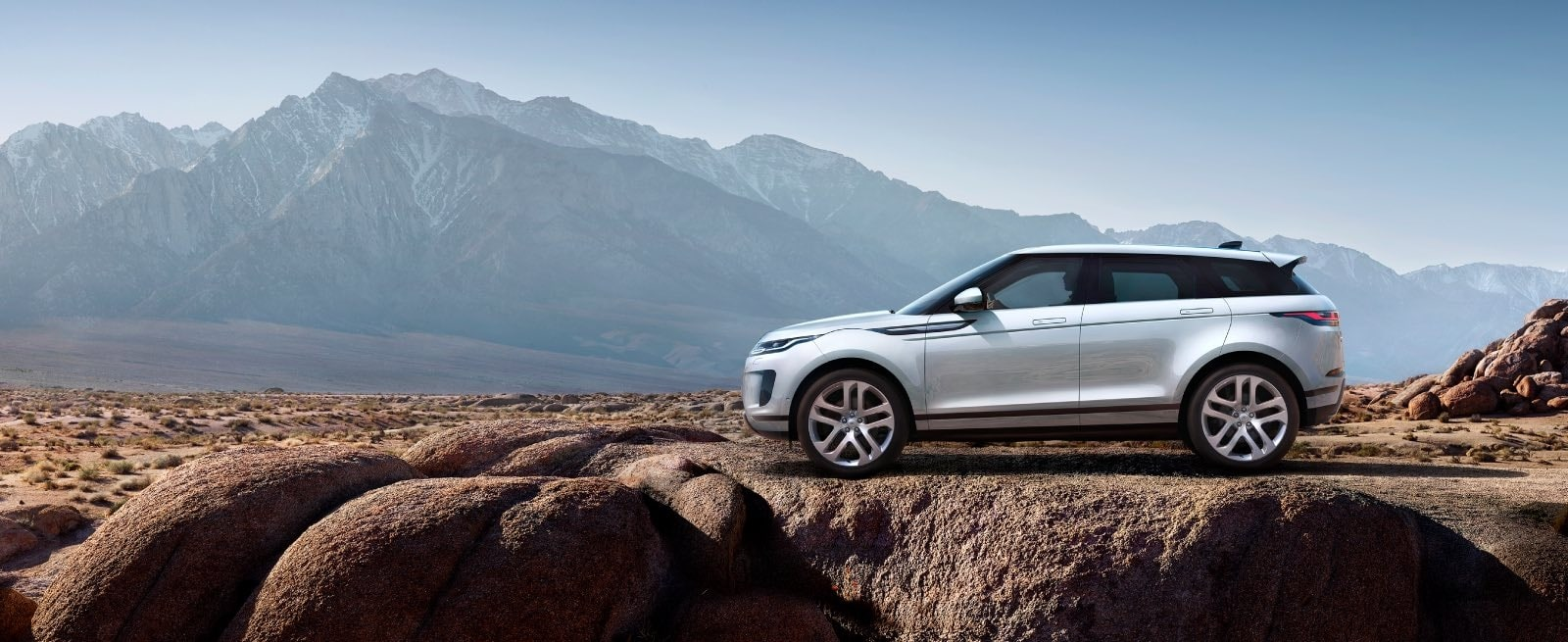 A White Range Rover Evoque Parked On The Edge of A Cliff
