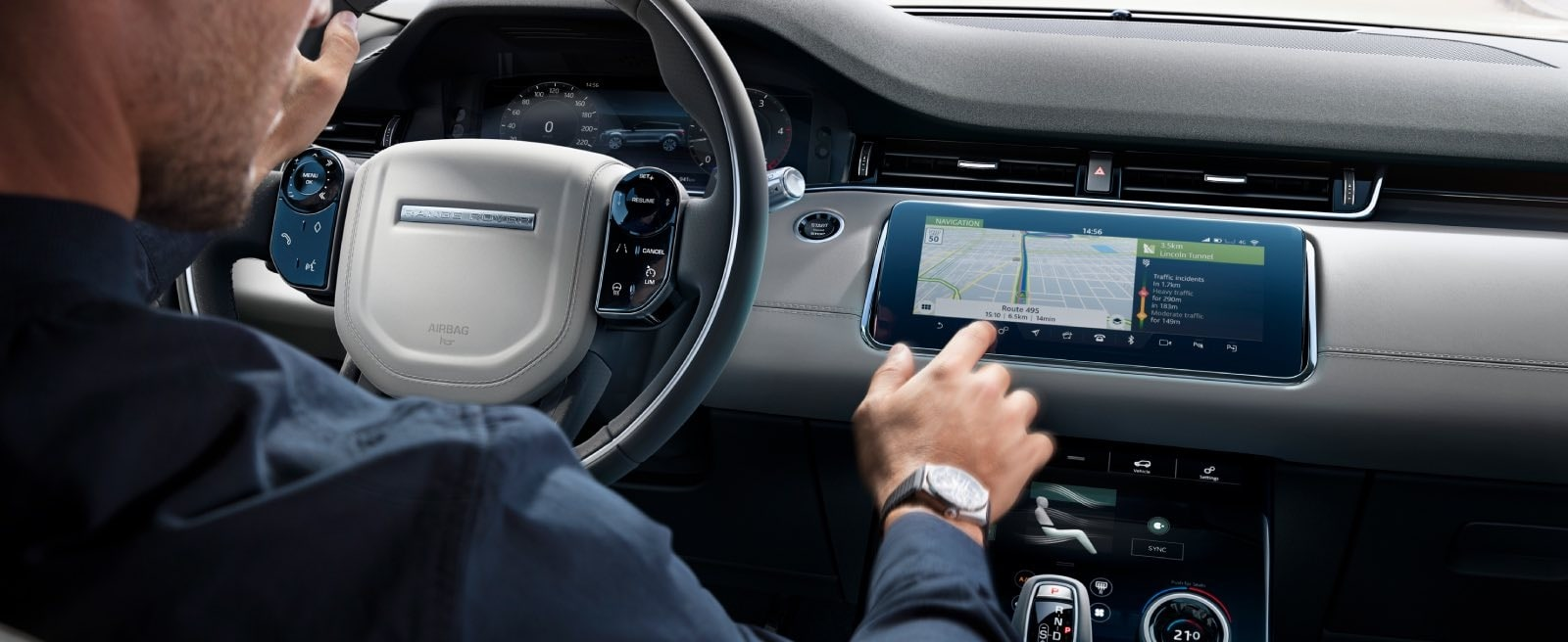 A Man Using The Infotainment System Onboard a Range Rover Evoque