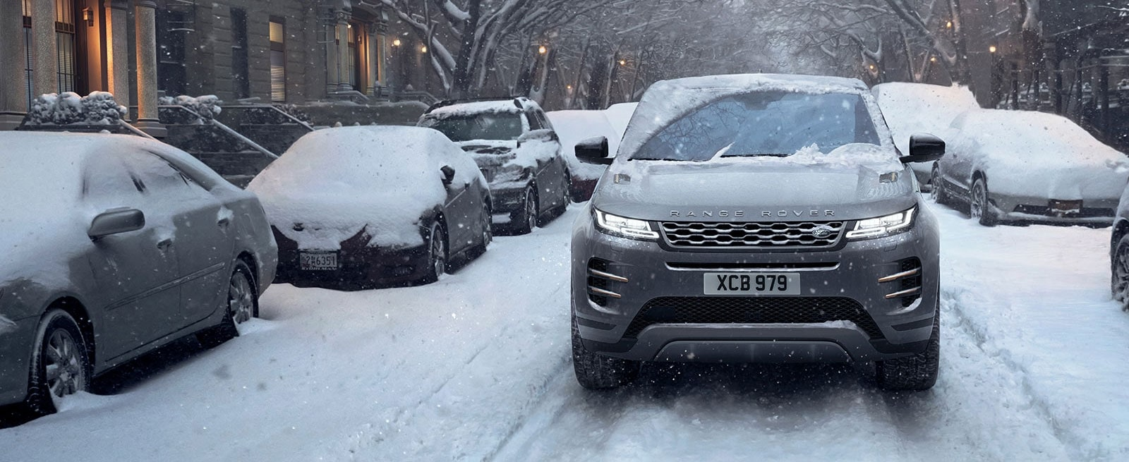 A Silver Range Rover Evoque Driving Down a Snow Covered City Street