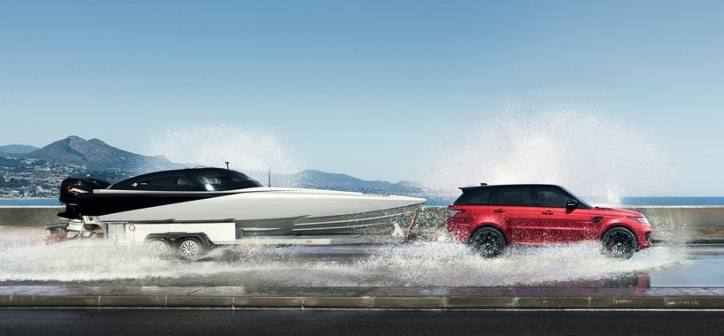 Red Range Rover Sport Towing A Speedboat Along a Coastal Road