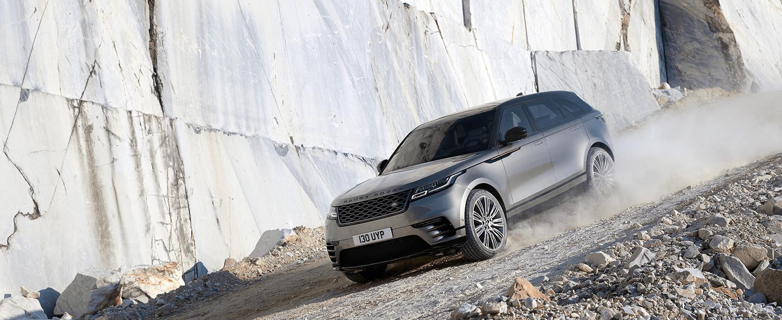 Silver Range Rover Velar Driving Off-Road Through a Quarry