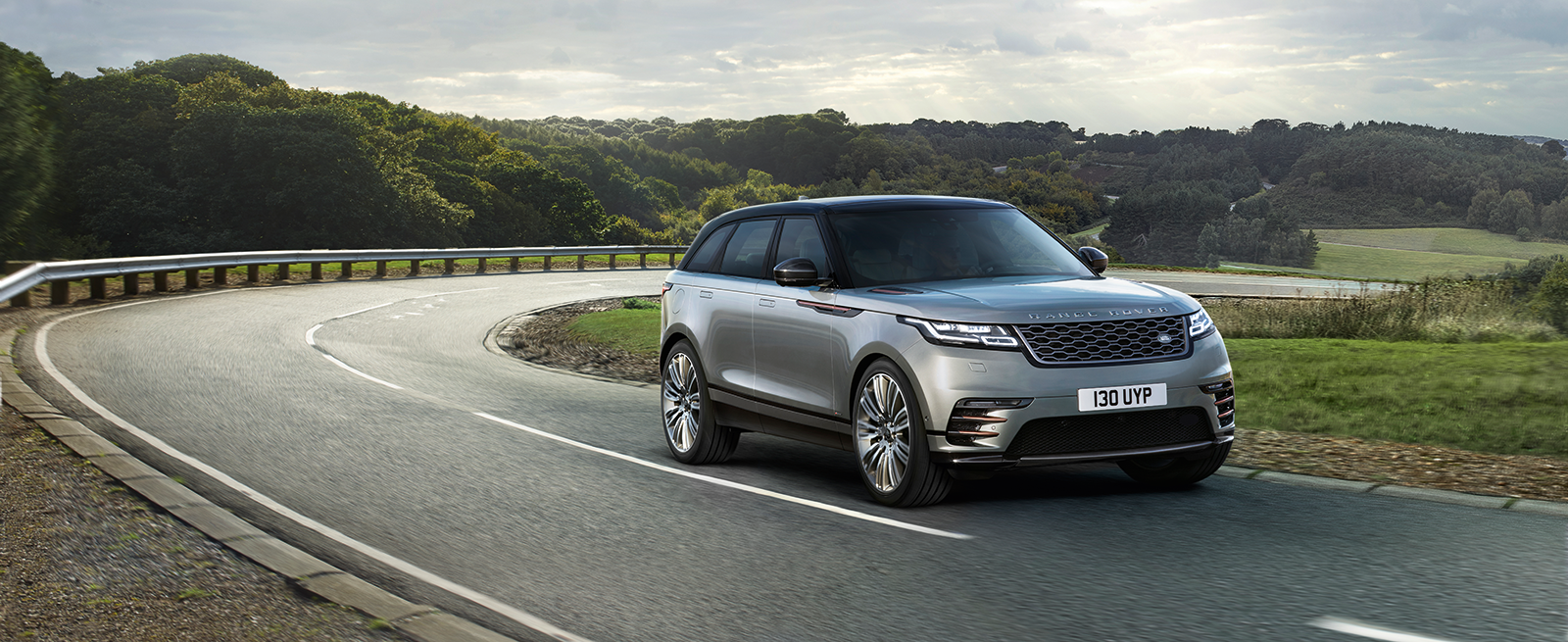 Silver Range Rover Velar Driving On A Winding Country Road